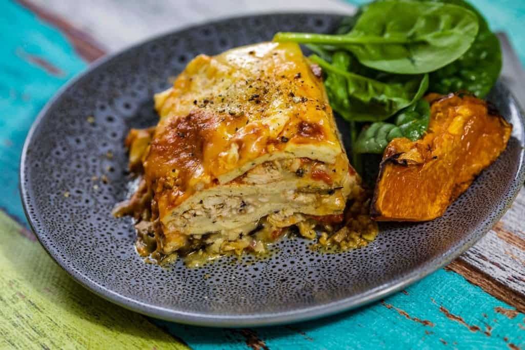 Chicken lasagne pumpkin and spinach on blue plate