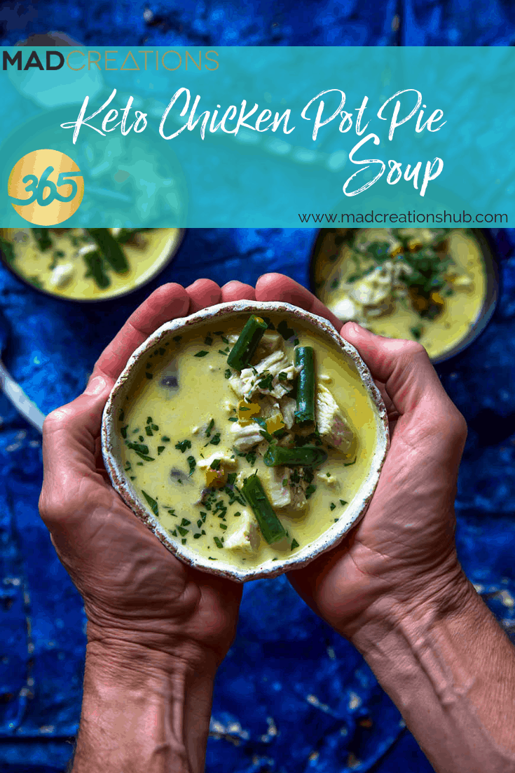 Mad Creations Keto Chicken Pot Pie Soup in 2 hands with blue background