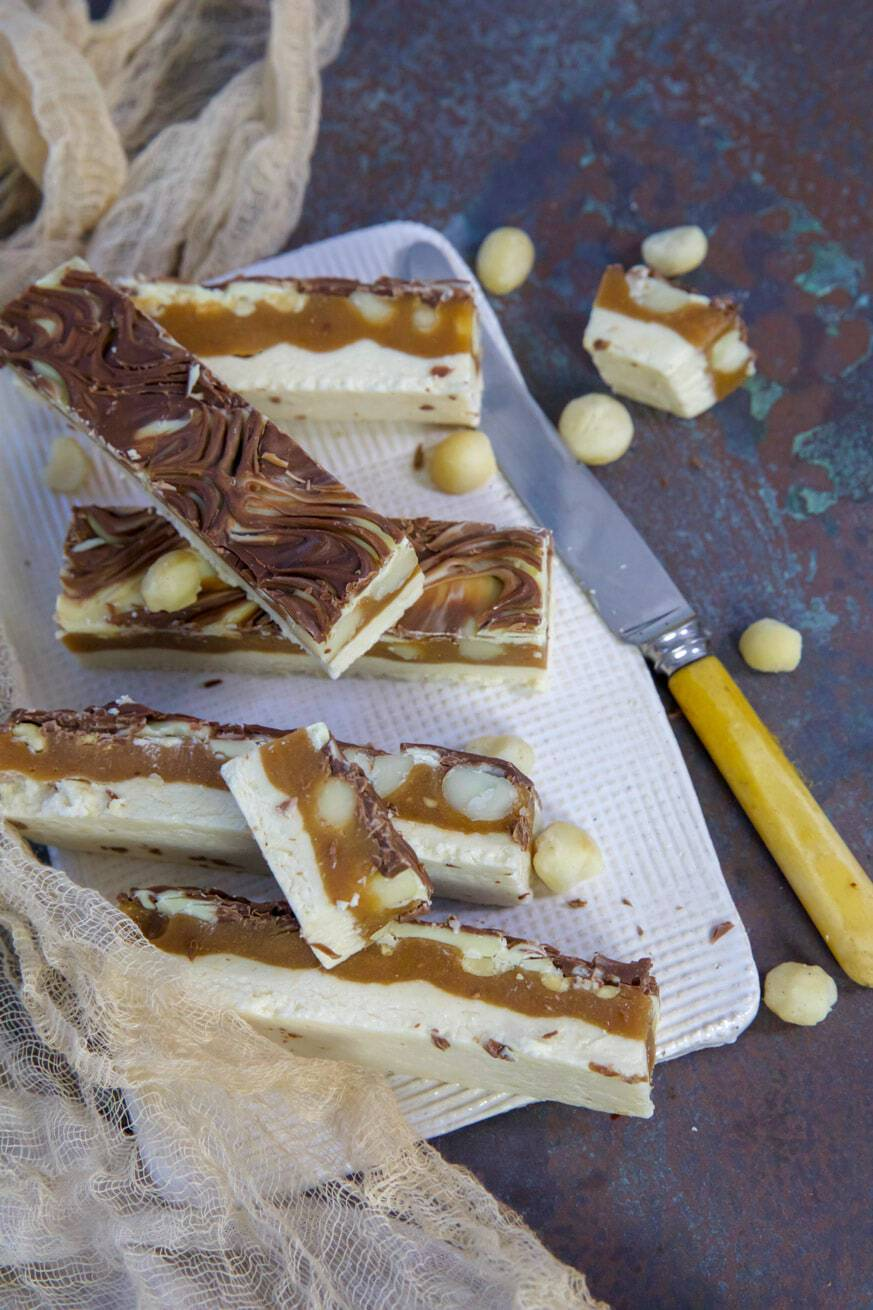 caramel chew bars on a white platter with knife