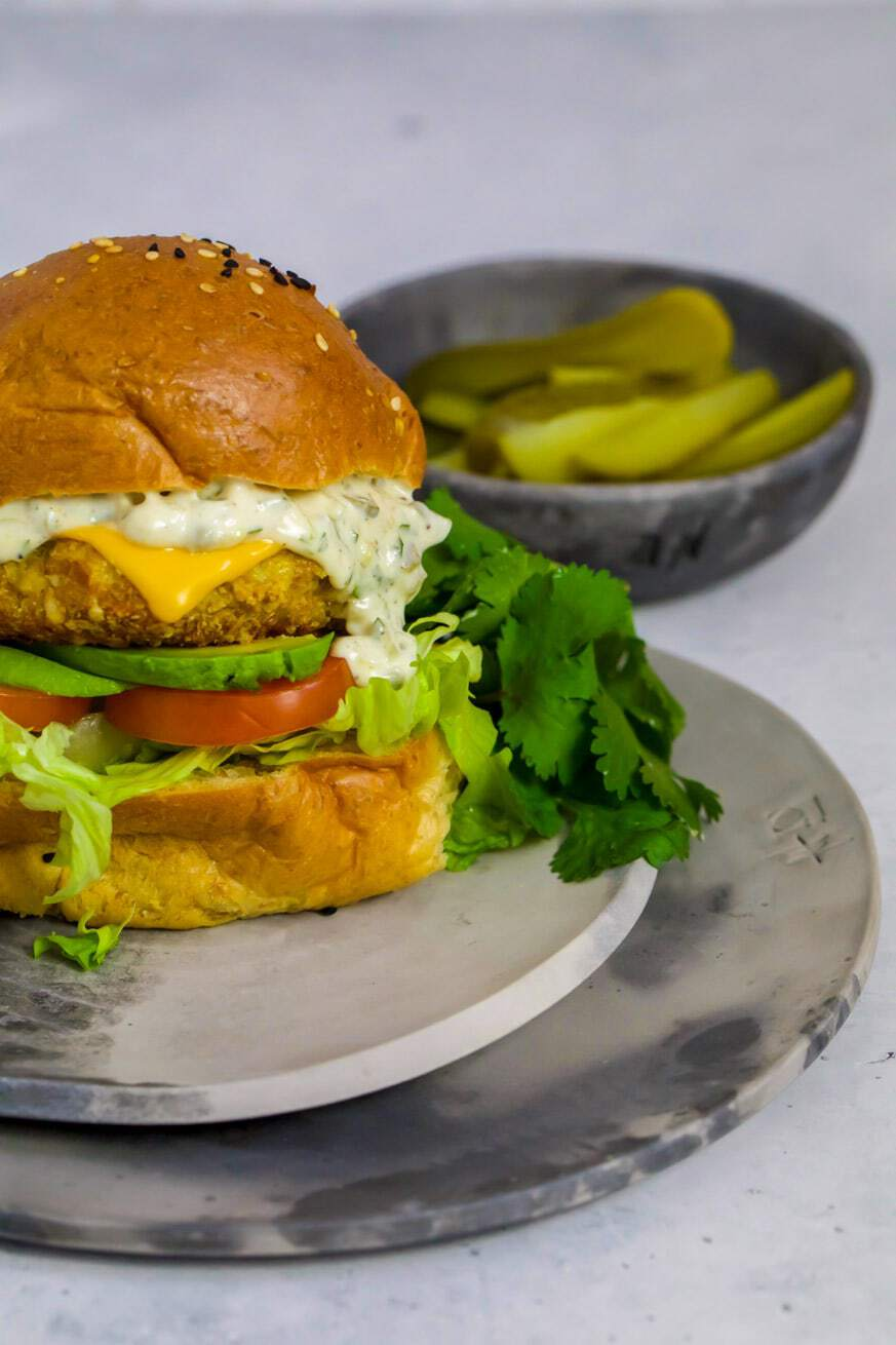 Fish burger on 2 grey plates with sides