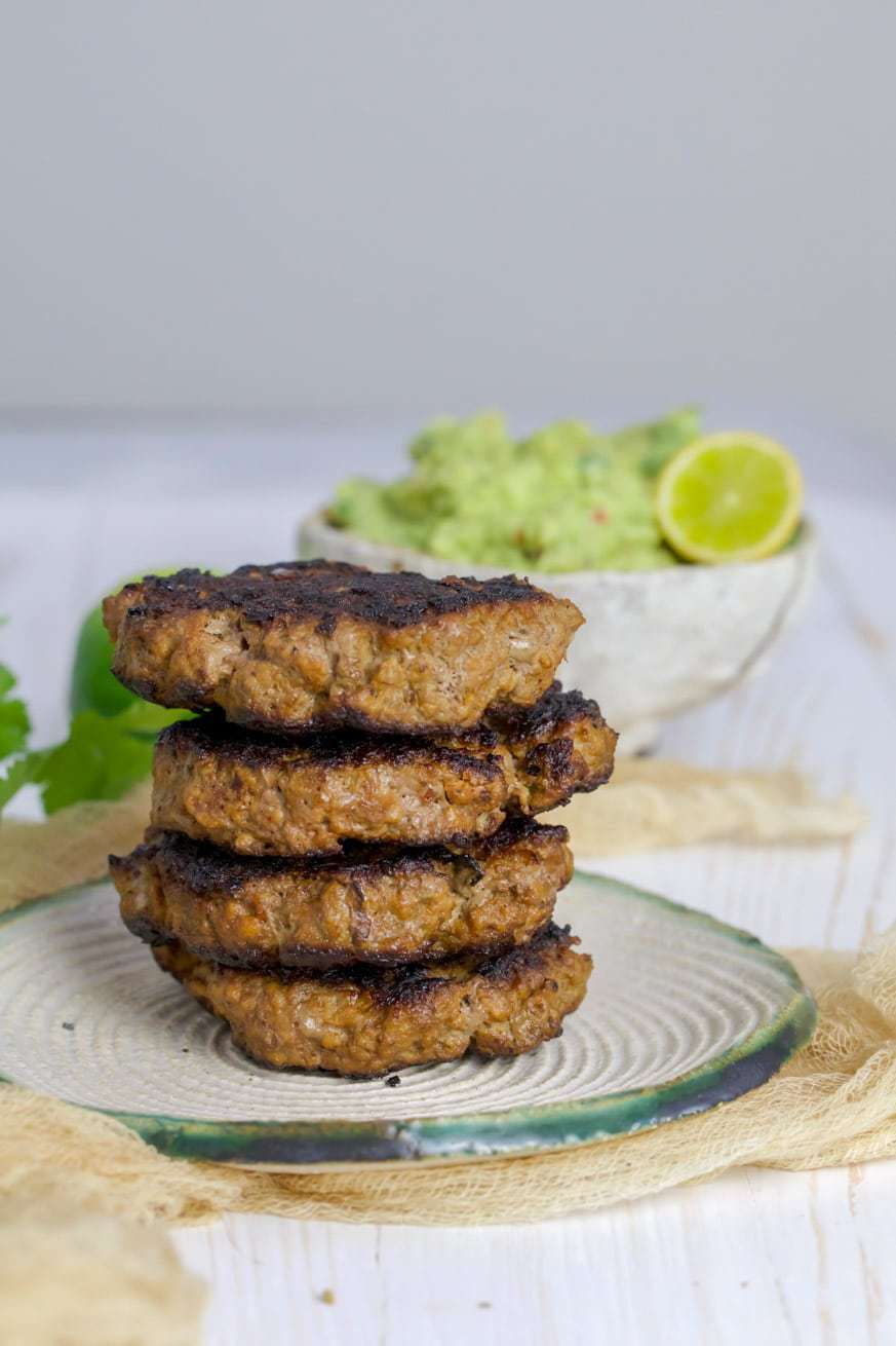 Beef patties stacked on a white plate