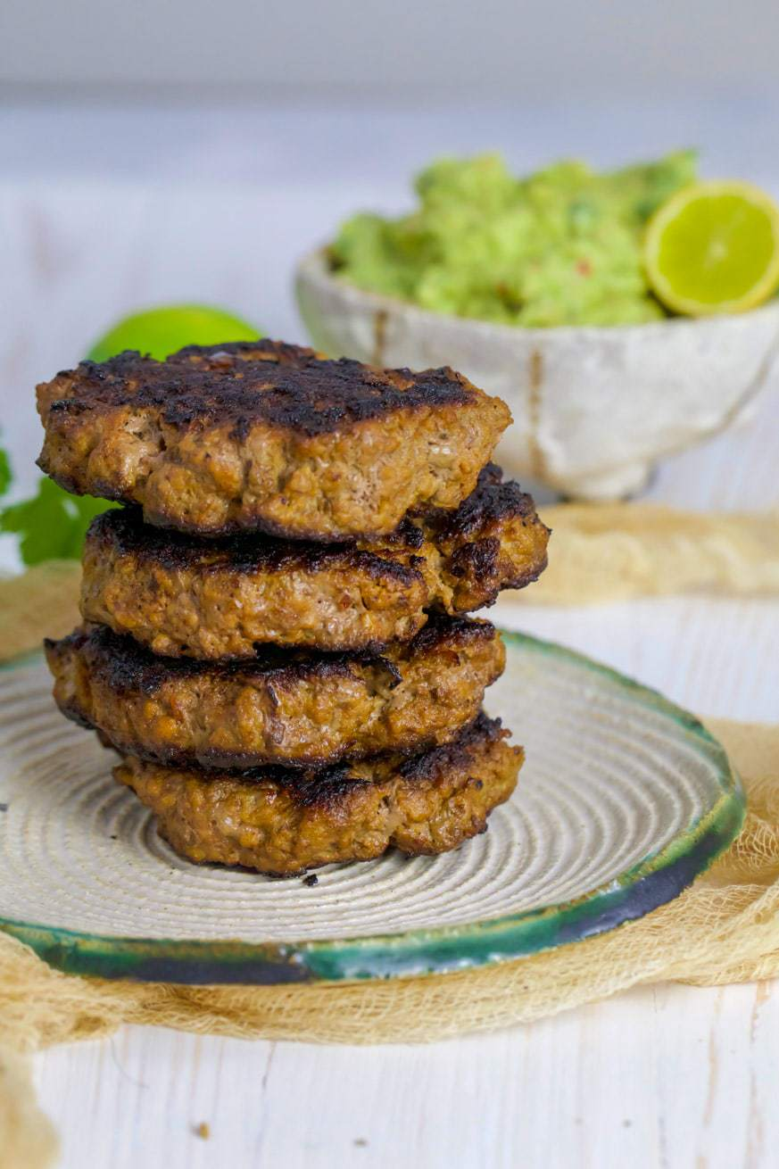 Stack of beef burgers on white plate