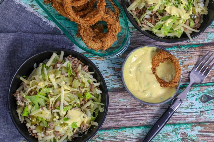 Big Mac Salad bowl with onion rings on a table