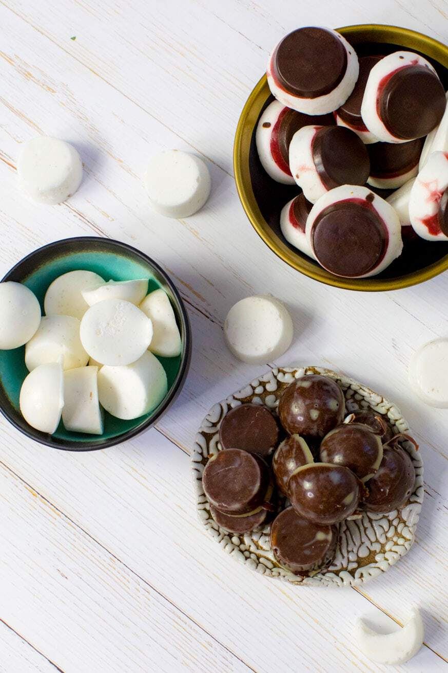 Mixed treats on plates on white table